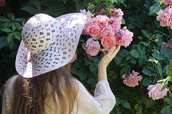 Woman with summer hat holding a pink petaled flower