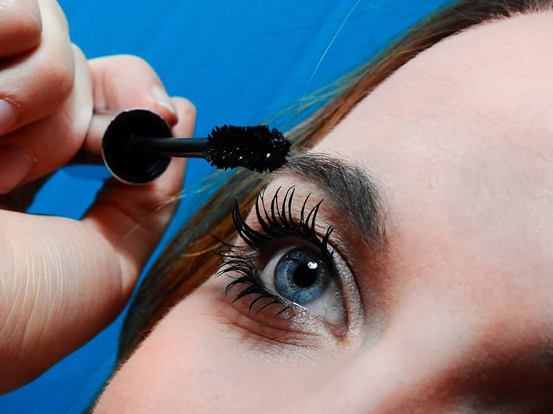 Woman putting mascara on her lashes