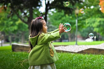 Girl playing bubbles in green grass field