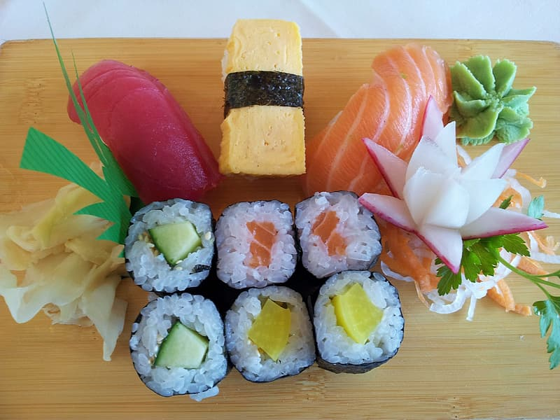 Variety of sushi on brown wooden panel