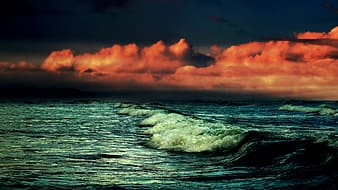 Ocean waves under orange and gray cloudy sky during sunset