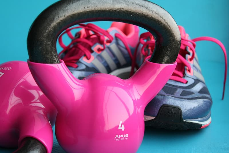 Close up photo of pink and black kettlebell and running shoes