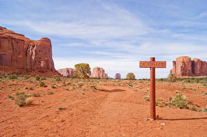 Brown rock formation near road close signage under blue and white cloudy sky during daytime