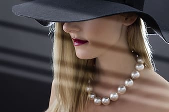 Woman in black hat and silver necklace