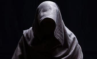 Person in white hijab covering face with white textile