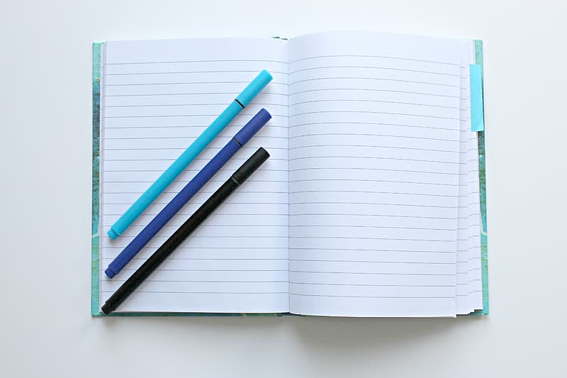 Three color pens on top of notebook