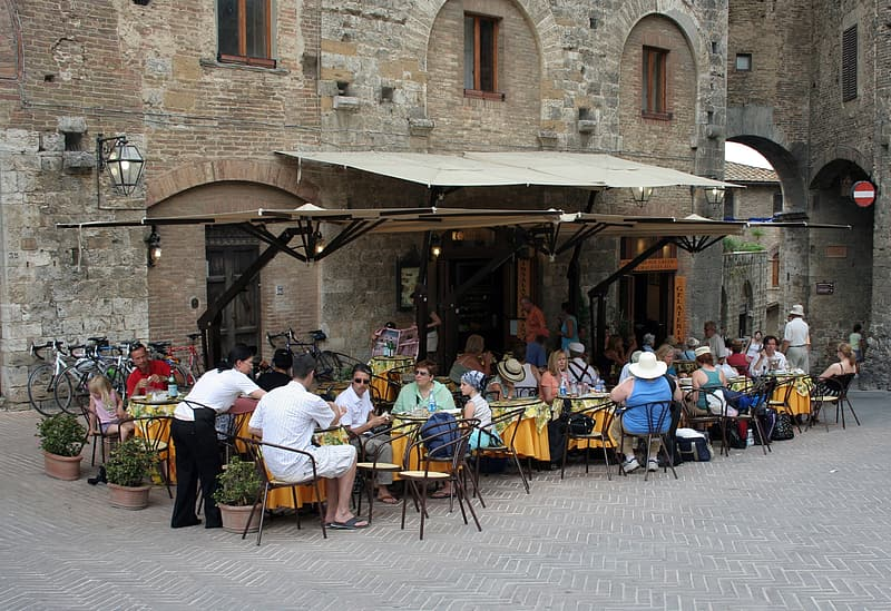 Group of people dining outside brown concrete building
