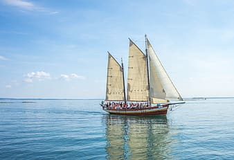 Group of people on sail ship above sea