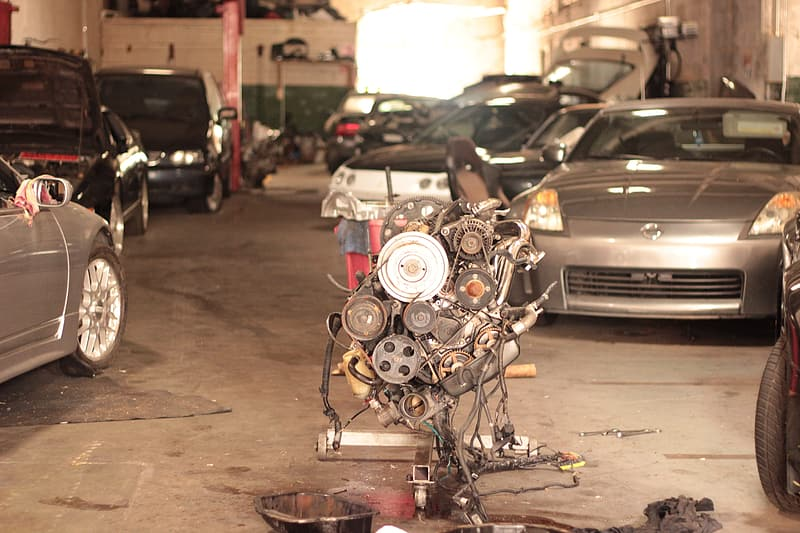 Vehicle engine on engine stand on garage with vehicles