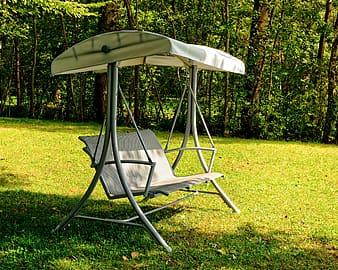 Gray and white canopy bench swing near green trees