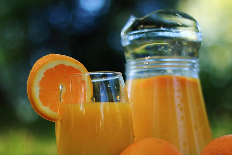 Selective focus photo of orange juice in glass pitcher and drinking glass with sliced orange fruit