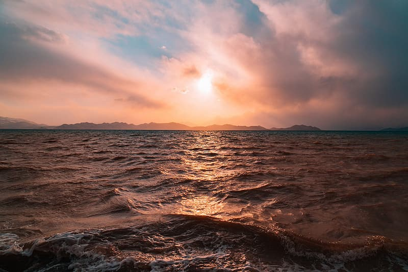 Body of water under golden hour and cloudy sky