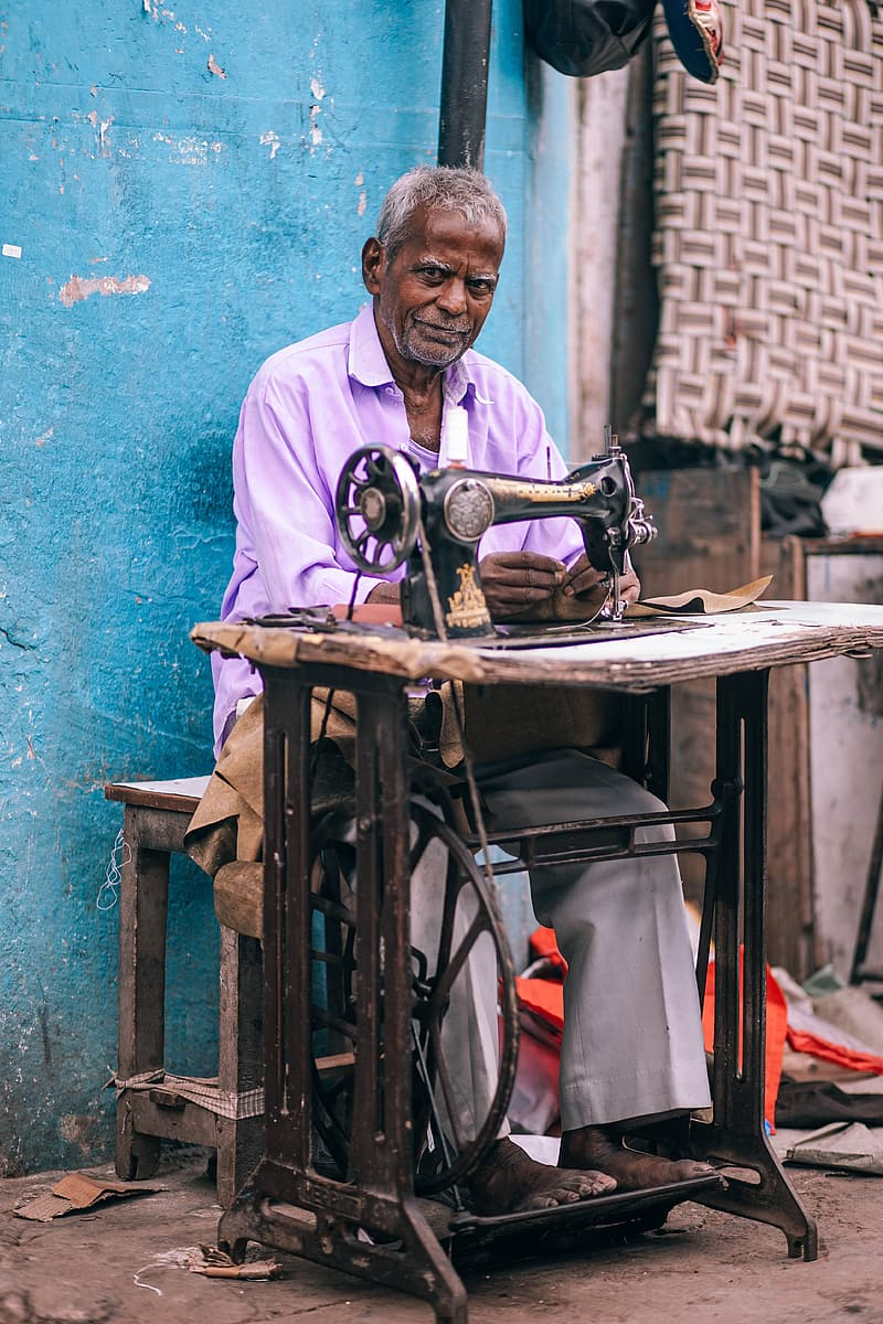 Man sitting on chair fixing textile by using sewing machine
