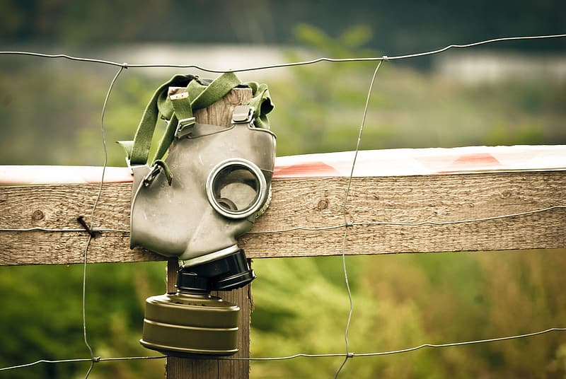 Gray gas mask hanging on wire fence