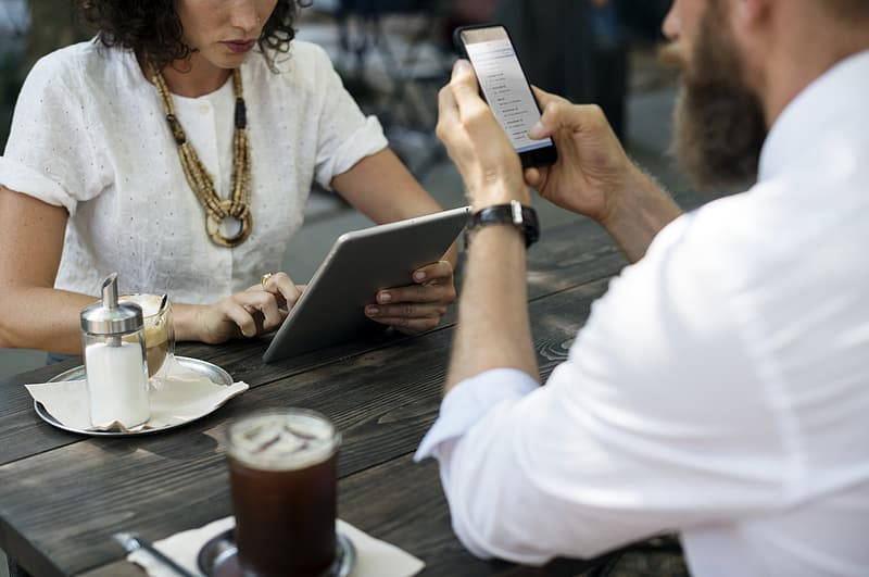 Man sitting holding smartphone in front of woman holding tablet