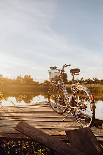 Bicycle with basket on the pier in bright sunset light