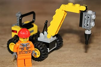 Worker minifigure and heavy equipment building block toy placed on brown surface