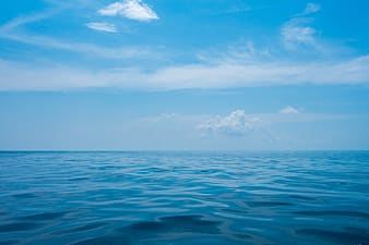 Blue ocean under blue sky and white clouds during daytime