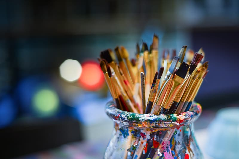 Brown paint brushes in clear glass jar