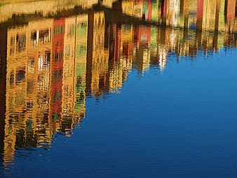 Assorted-color building reflecting on body of water at daytime