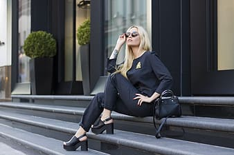 Woman wearing black long-sleeved shirt with black pants outfit sitting on stairs