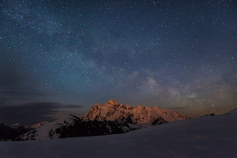 Snow covered mountain under starry night