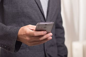 Man in black suit holding HTC One M8 smartphone