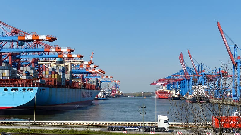 Blue and red cargo ship on sea under blue sky during daytime