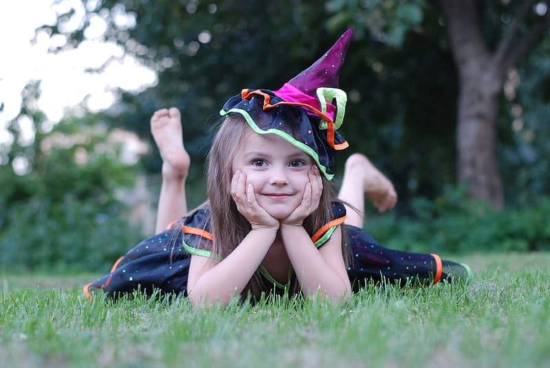 Shallow focus photography of girl wearing black witch costume on grass field