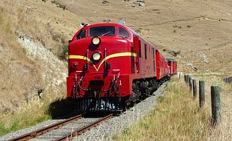 Red train on rail tracks during daytime