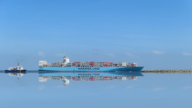 Red and white cargo ship on sea under blue sky during daytime