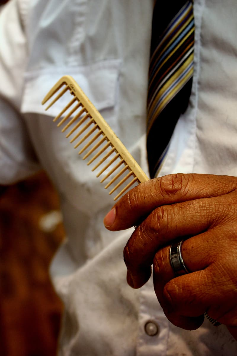Person wearing silver ring holding white plastic comb