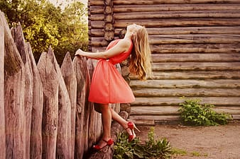 Woman wearing orange cocktail dress holding on fence
