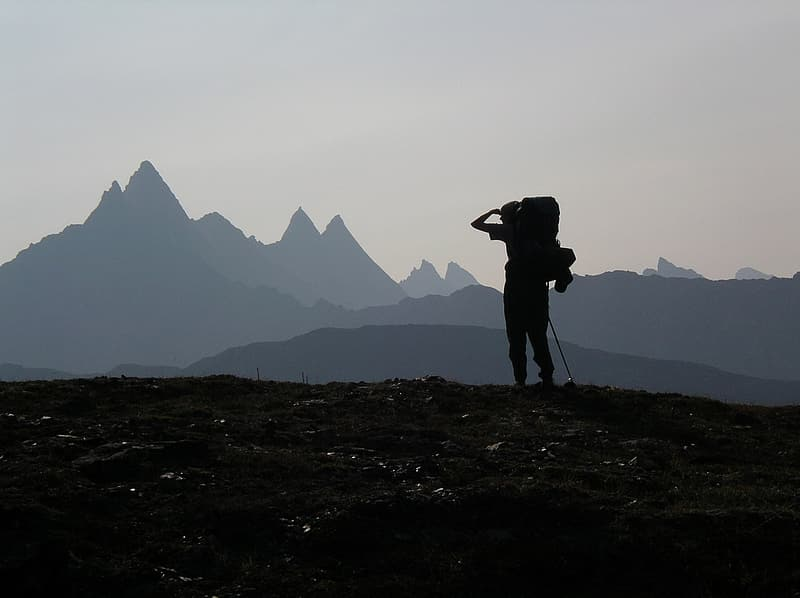 Silhouette of person carrying hiking backpack standing near mountain