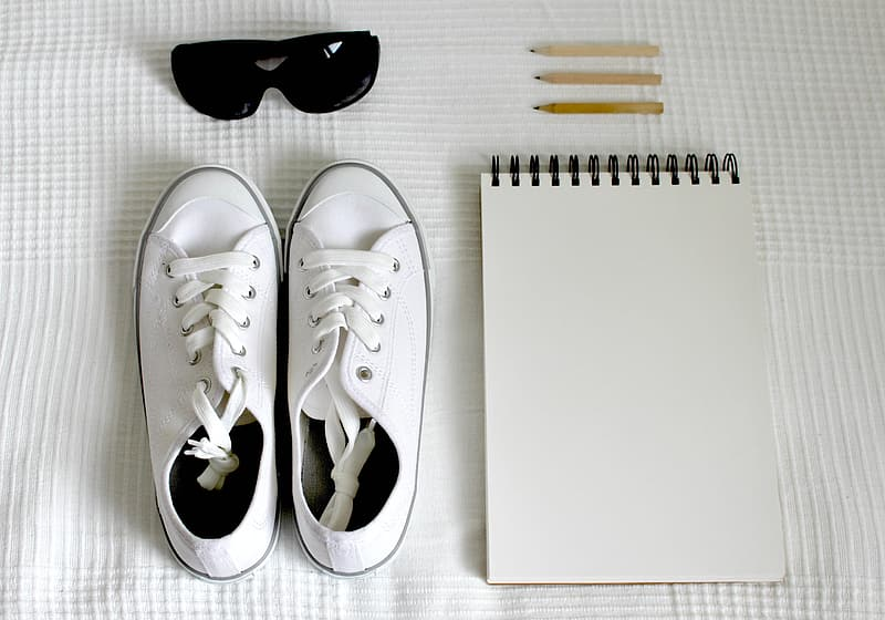 Pair of white low-top sneakers near the white notebook