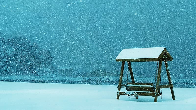 Brown wooden table on snow covered ground during daytime