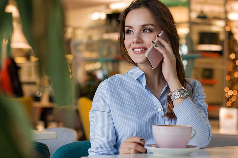 Woman in blue dress shirt holding white smartphone