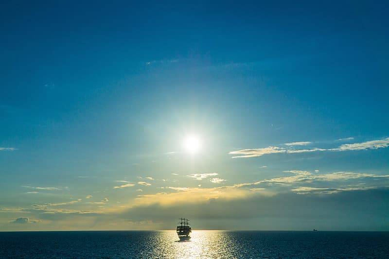 Silhouette of boat on sea under blue sky during daytime