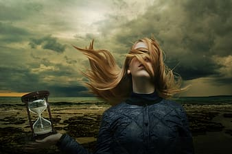 Photo of woman holding sand hour glass near seashore under nimbus clouds