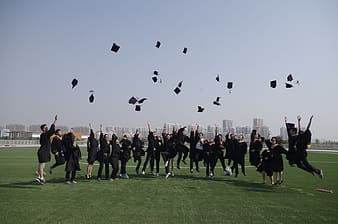 Graduates throws their mortar boards up in grass field during daytime