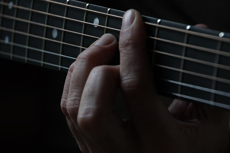 Person holding guitar strings
