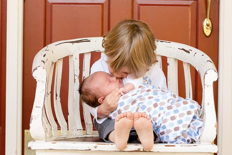 Girl kissing the baby while sitting on chair