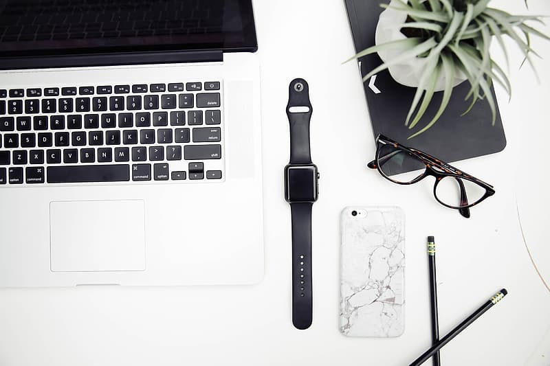 Space gray aluminum case Apple Watch with black sports band near black frame wayfarer style eyeglasses and MacBook Pro