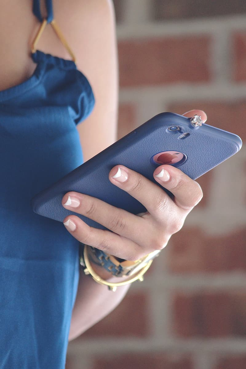 Woman holding iPhone with blue case