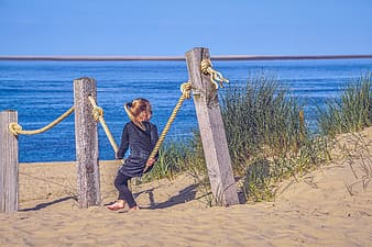 Woman in black long sleeve shirt sitting on brown wooden post near body of water during