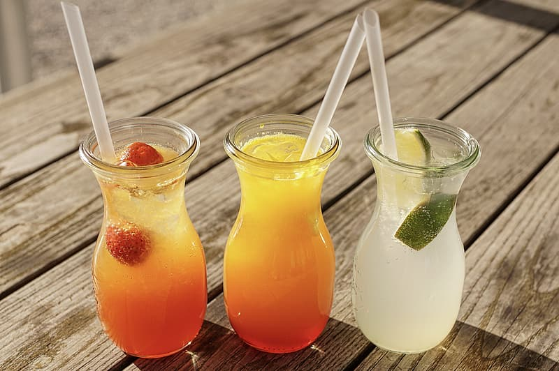 Three clear drinking glasses with orange liquid and ice cubes