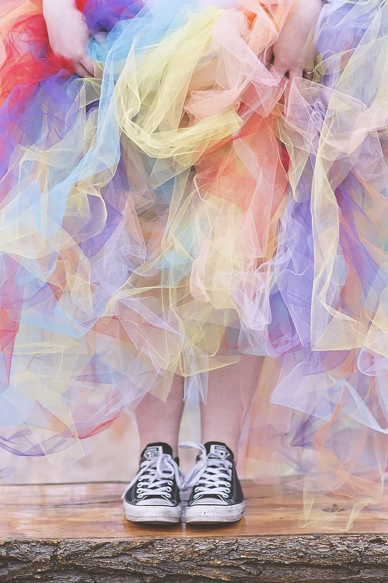 Woman wearing pair of black Converse All-Star low top sneakers and assorted colored skirt
