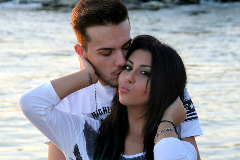 Man kissing woman standing near body of water