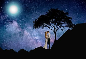Woman in white dress standing on rock under starry night