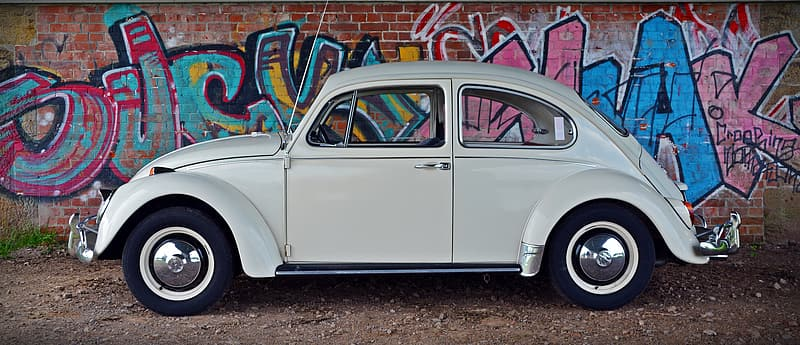 White Volkswagen Beetle parked beside wall